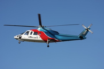 white, red, and blue air ambulance flying