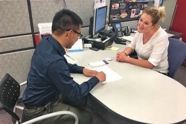 man getting help from AMA travel insurance specialist