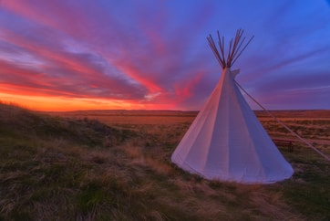 tipi on prairies with sunset