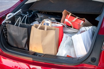 red car's trunk full of shopping bags