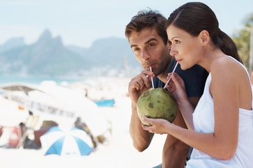 man and woman drinking from a coconut