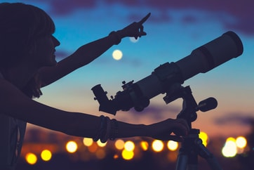 woman with telescope pointing at constellations in sky
