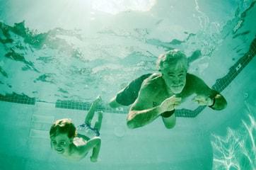 grandpa and grandson swimming in pool