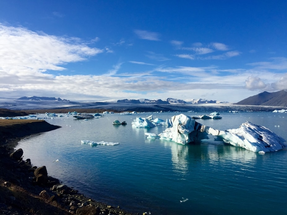 Icebergs in a lagoon with glaciers and mountains in the distance