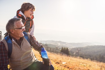man and grandson taking a break from exploring hill side