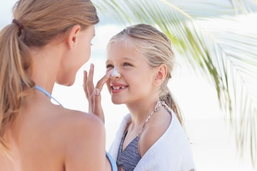 mom applying sunscreen to daughter's nose