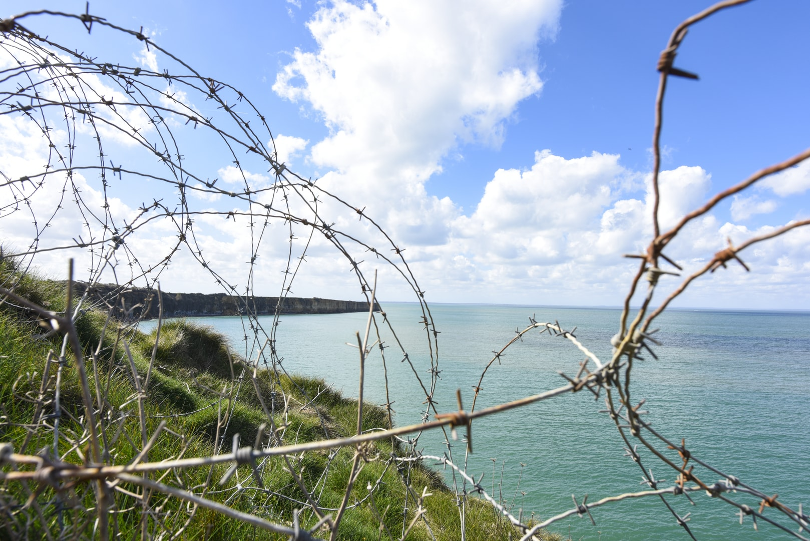 Normandy's cliffs with barbed wire in foreground