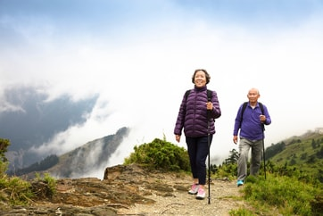 older couple hiking up mountain trail