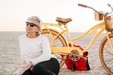 older lady sitting on beach beside her bike