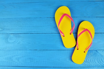 pair of yellow flip flops on blue deck